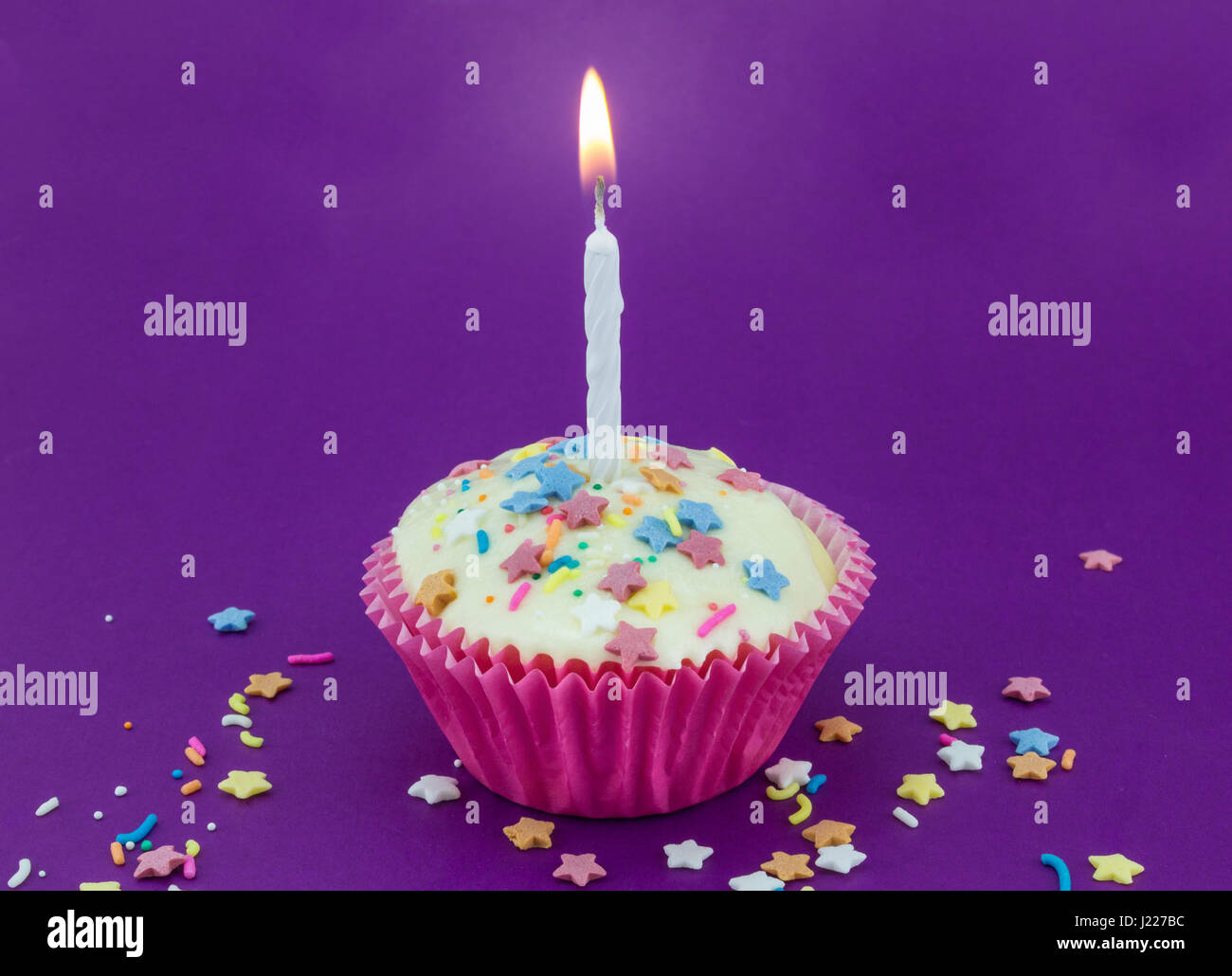 Bright purple background with single white cup cake in pink paper case and lit candle with colour star sprinkles - Stock Image