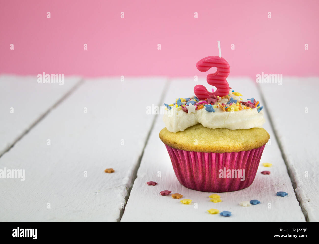 Happy birthday cup cake with star sprinkles and number 3 pink candle on white table with pink background - Birthday - Stock Image