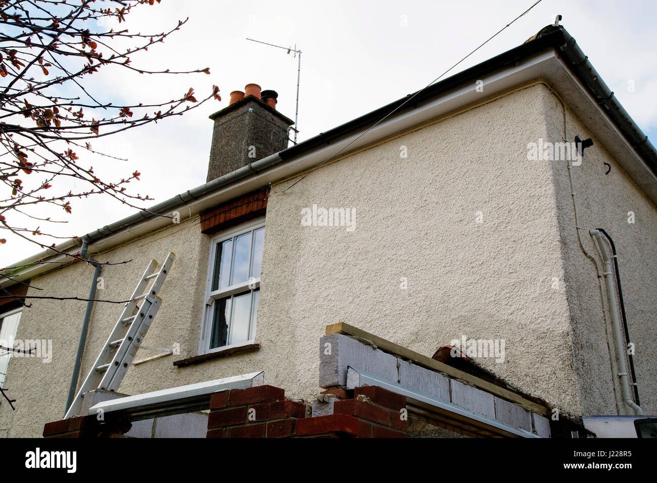 Refurbishment work in progress on a semi-detached house with rendered frontage and part-built porch. A ladder leans - Stock Image