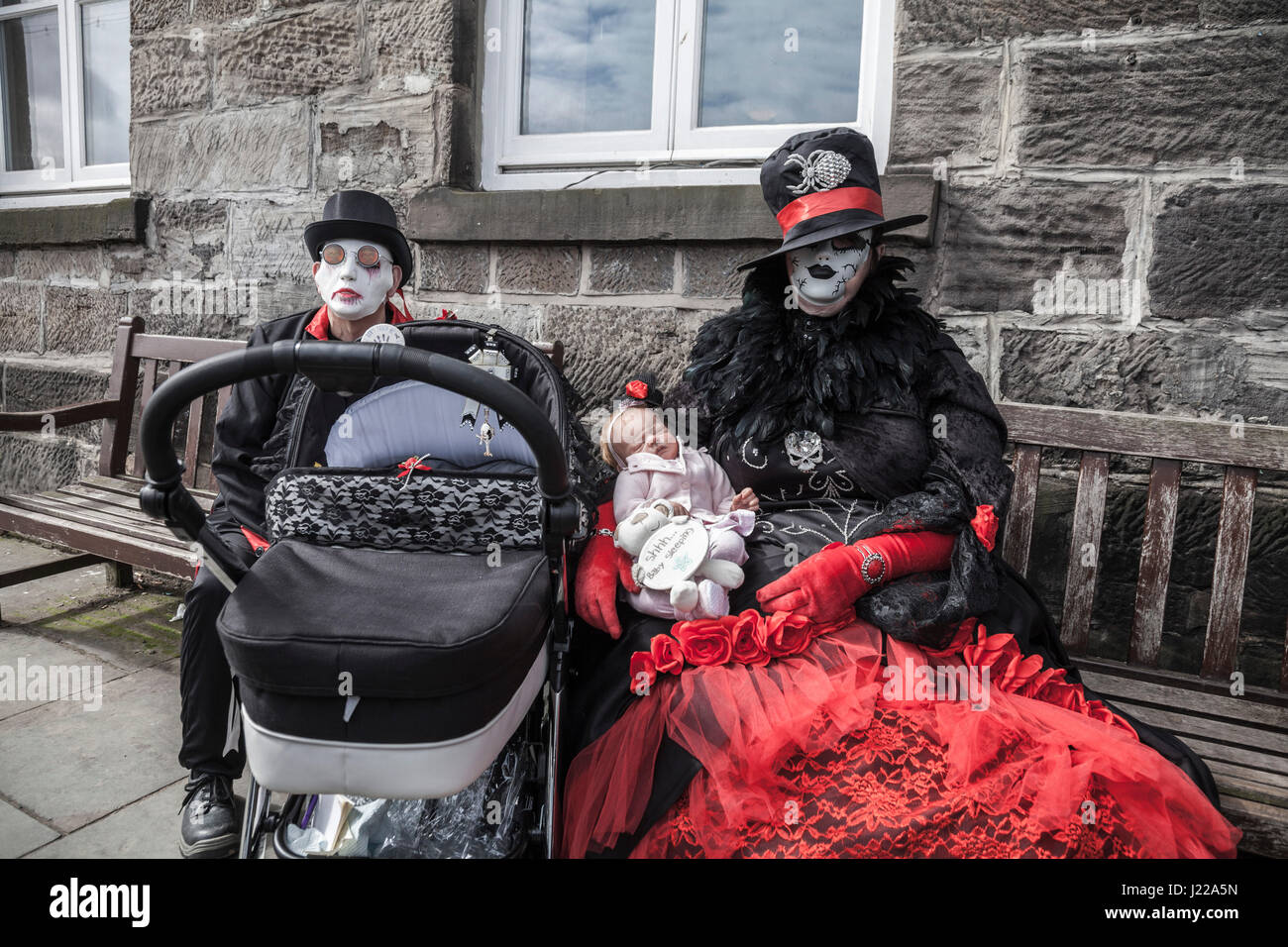 A male and female Goth sit on benches at the seaside at the Whitby Goth Weekend and she cradles a lifelike baby - Stock Image