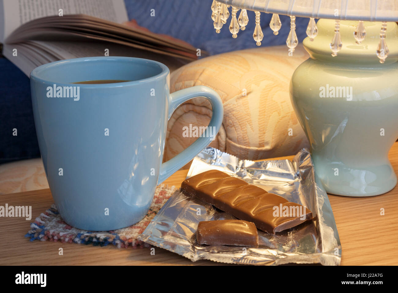 Everyday lifestyle homely hygge scene of a person relaxing reading a book with mug of coffee and chocolate by a - Stock Image