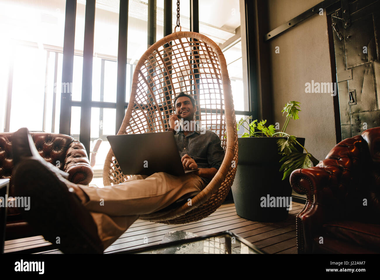 Young man sitting on a wicker hanging chair in office lounge with laptop and talking on mobile phone. Business man - Stock Image