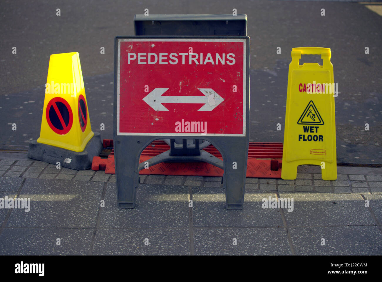 pedestrians this way sign on road path with wet floors warning - Stock Image