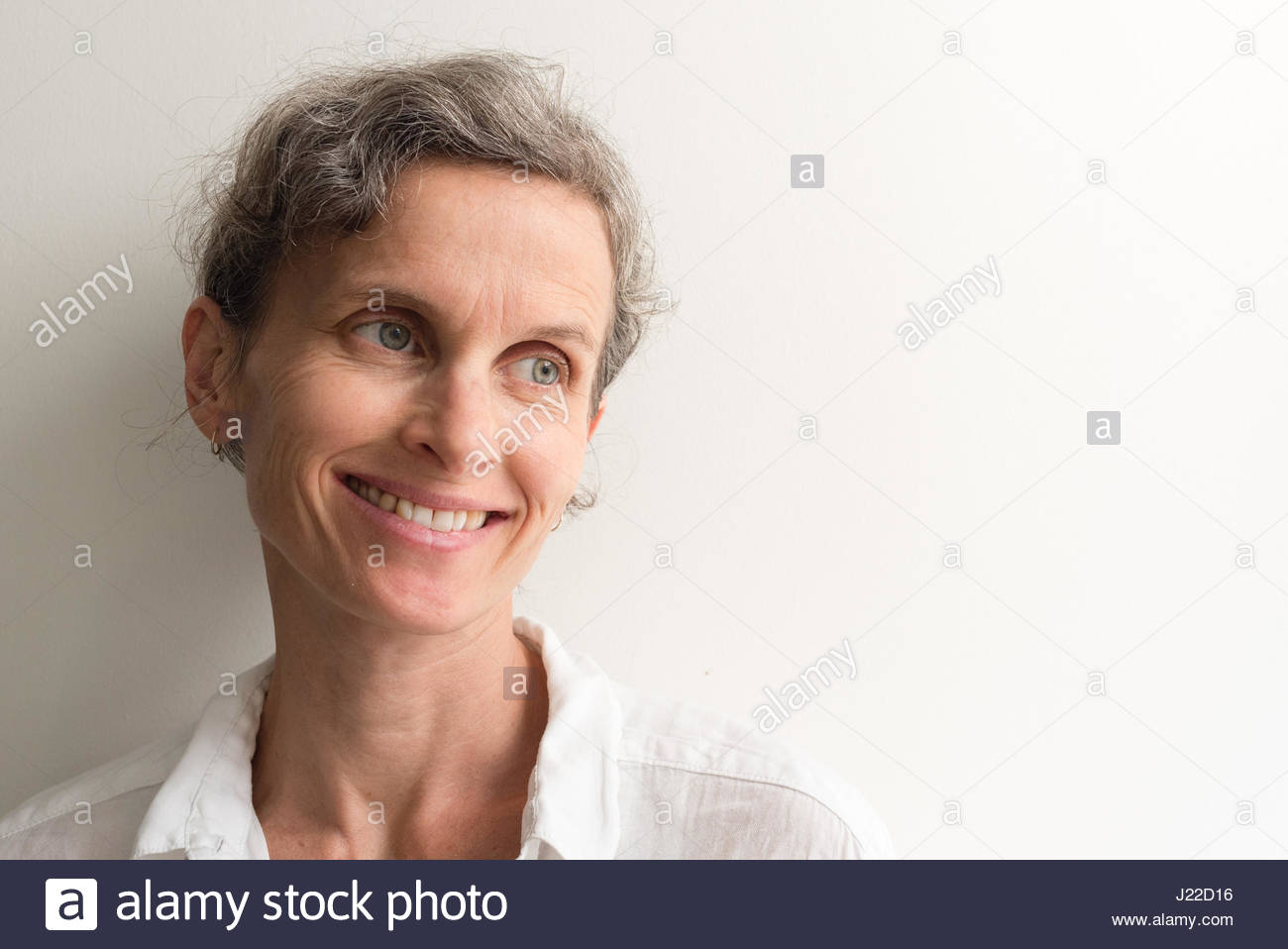 Head and shoulders view of middle aged woman with grey hair smiling (selective focus) - Stock Image