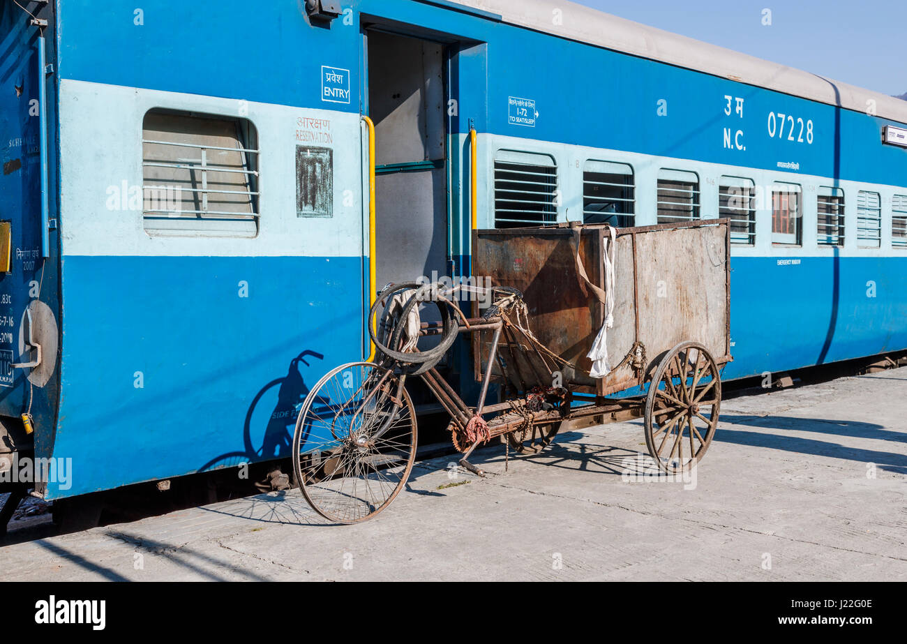 Battered, worn out tricycle next to a railway carriage at Kathgodam Station, Nainital District, Uttarakand, northern - Stock Image