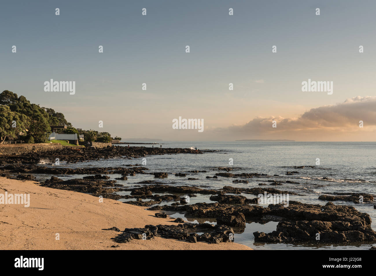 Auckland, New Zealand - March 2, 2017: Black volcanic north shore of Tapapuna Beach shows upcoming storm clouds - Stock Image