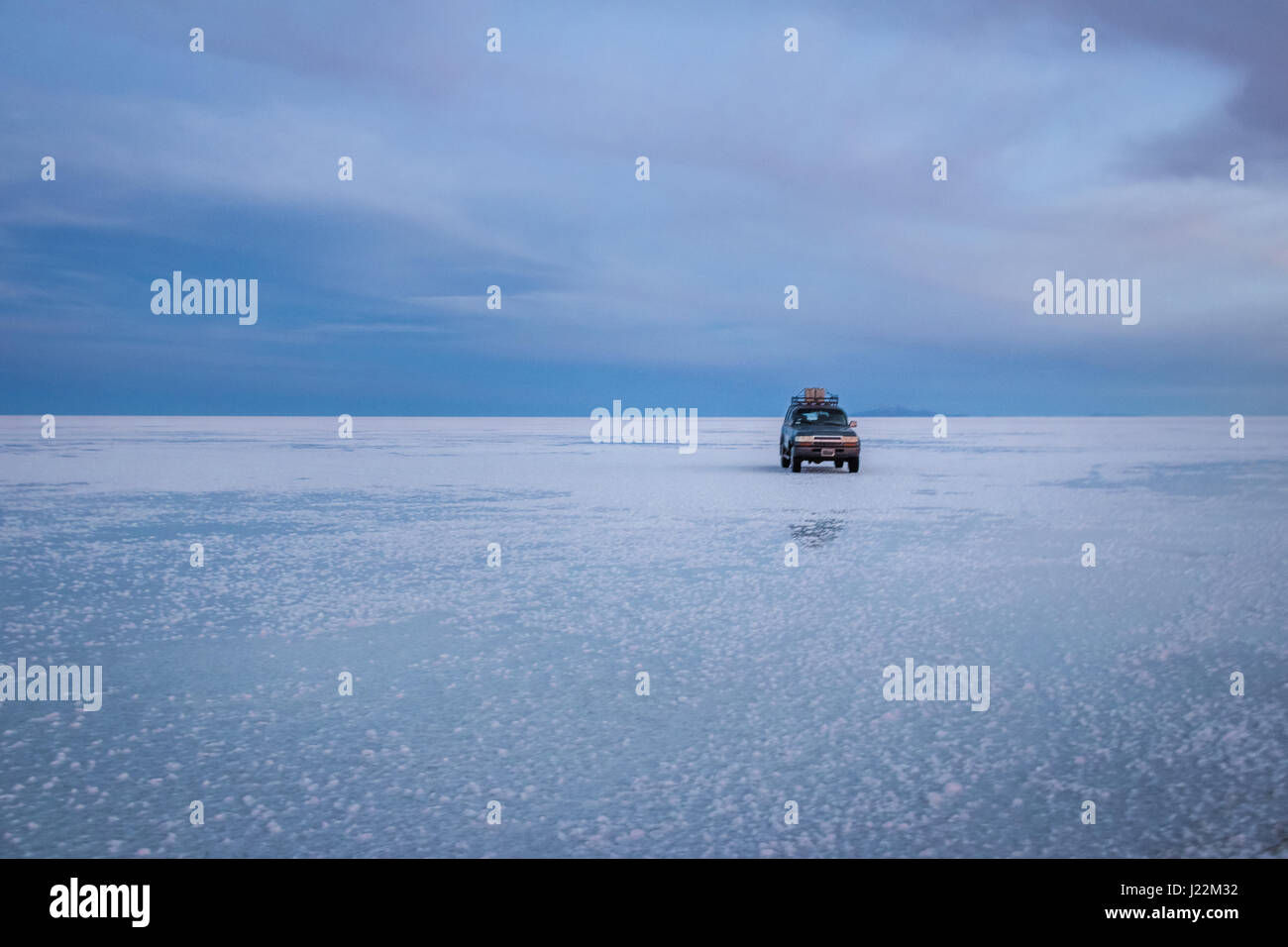 Off-road vehicle at sunrise in Salar de Uyuni salt flat - Potosi Department, Bolivia - Stock Image