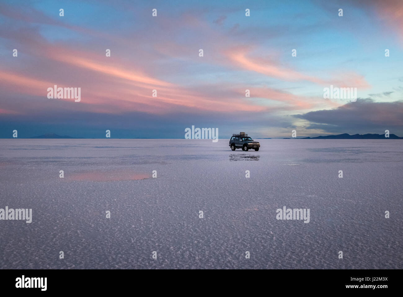 Off-road vehicle at sunrise in Salar de Uyuni salt flat - Potosi Department, Bolivia - Stock Image