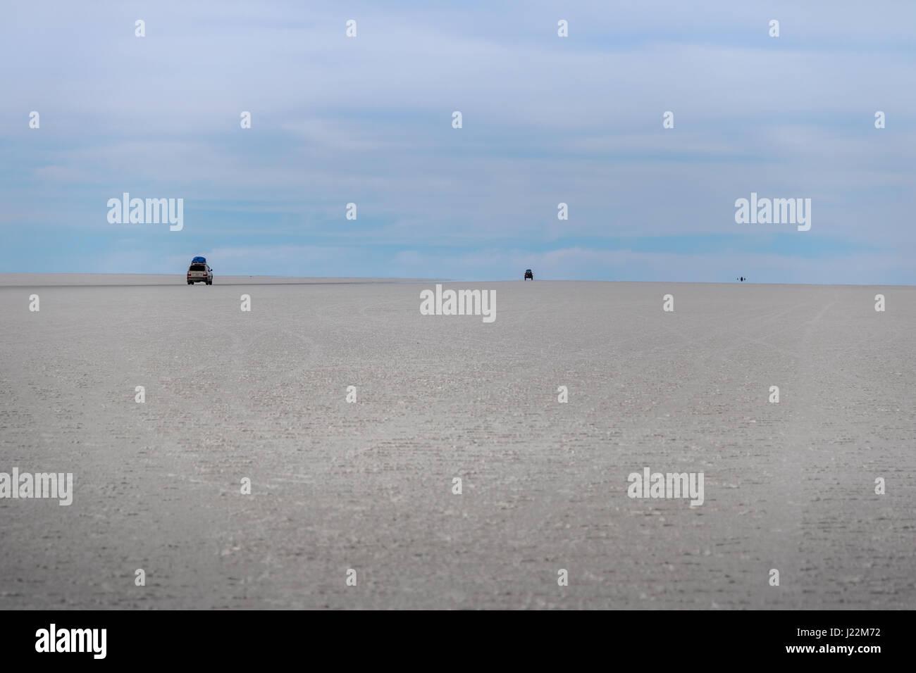 Cars disappearing into horizon in Salar de Uyuni salt flat - Potosi Department, Bolivia - Stock Image