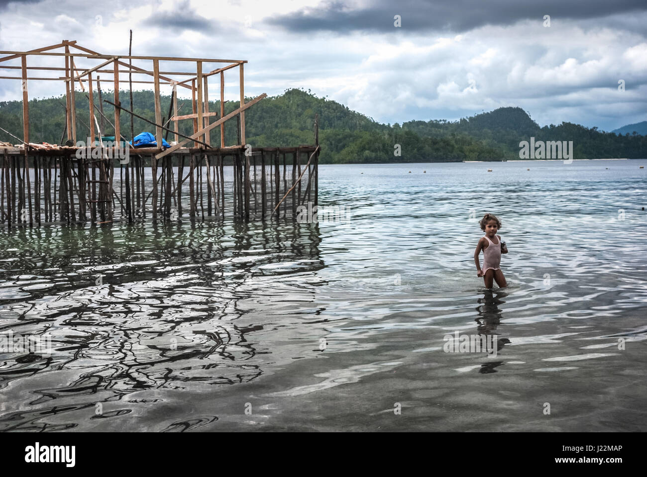 A little girl playing in the coastal water of Friwen Island in Raja Ampat Archipelago, West Papua, Indonesia. © - Stock Image