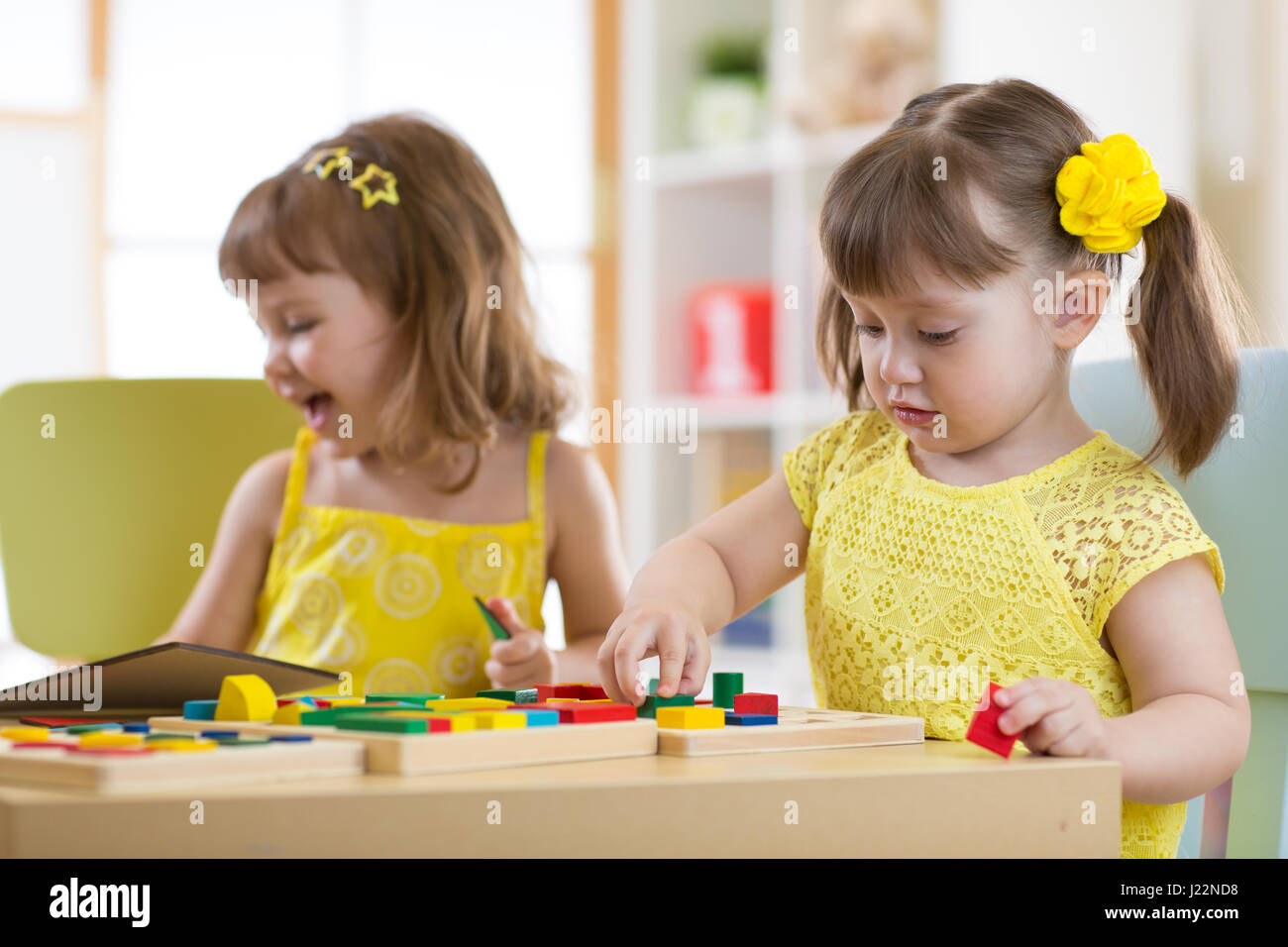 Preschool children playing with educational sorter toys in classroom, kindergarten or home - Stock Image