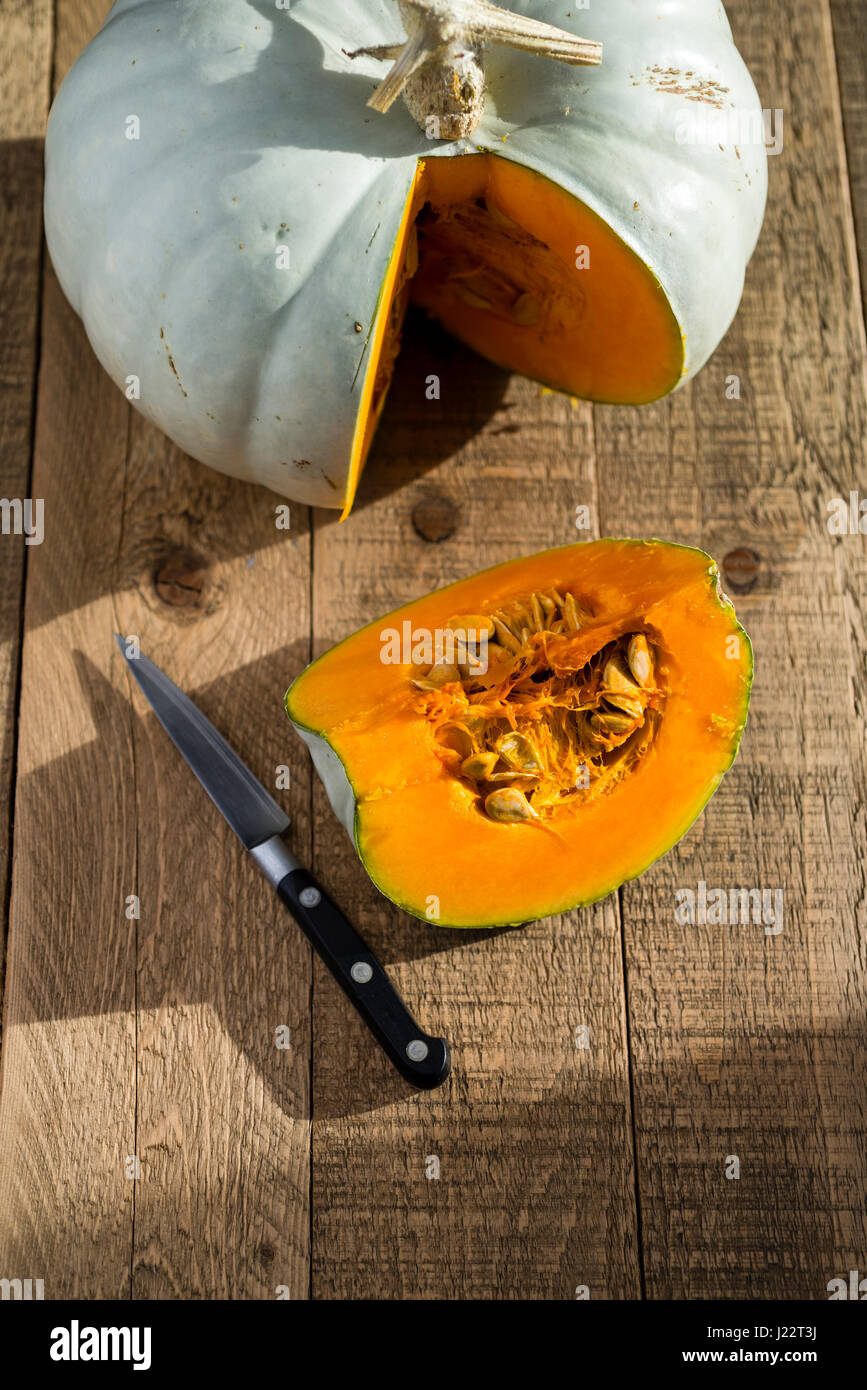 A Crown Prince Squash being cut and prepared for cooking on a wooden table. - Stock Image