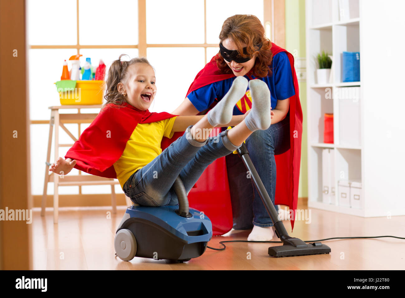 Super hero kid flying on vacuum cleaner. Mother and child daughter cleaning the room and have a fun - Stock Image