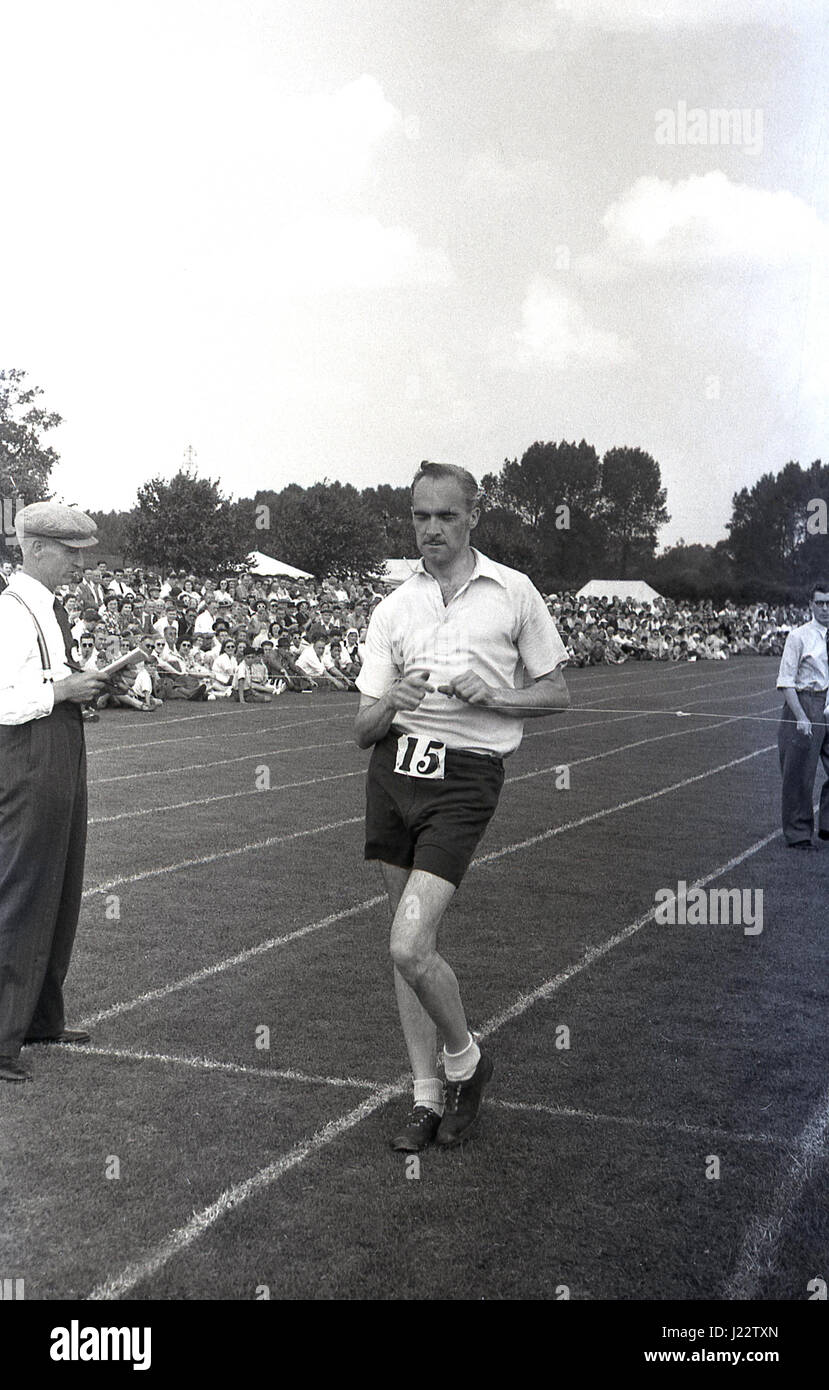 1950s, historical, male race walker hits the finishing tape at an amateur athletics meeting outdoors on a grass - Stock Image