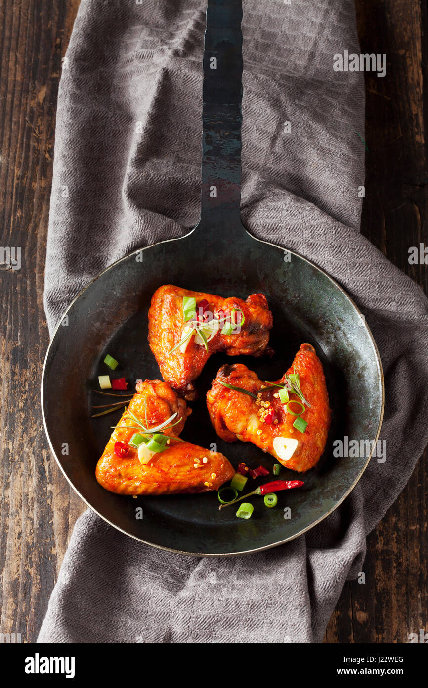 Three marinated and grilled chicken wings in cast-iron frying pan - Stock Image