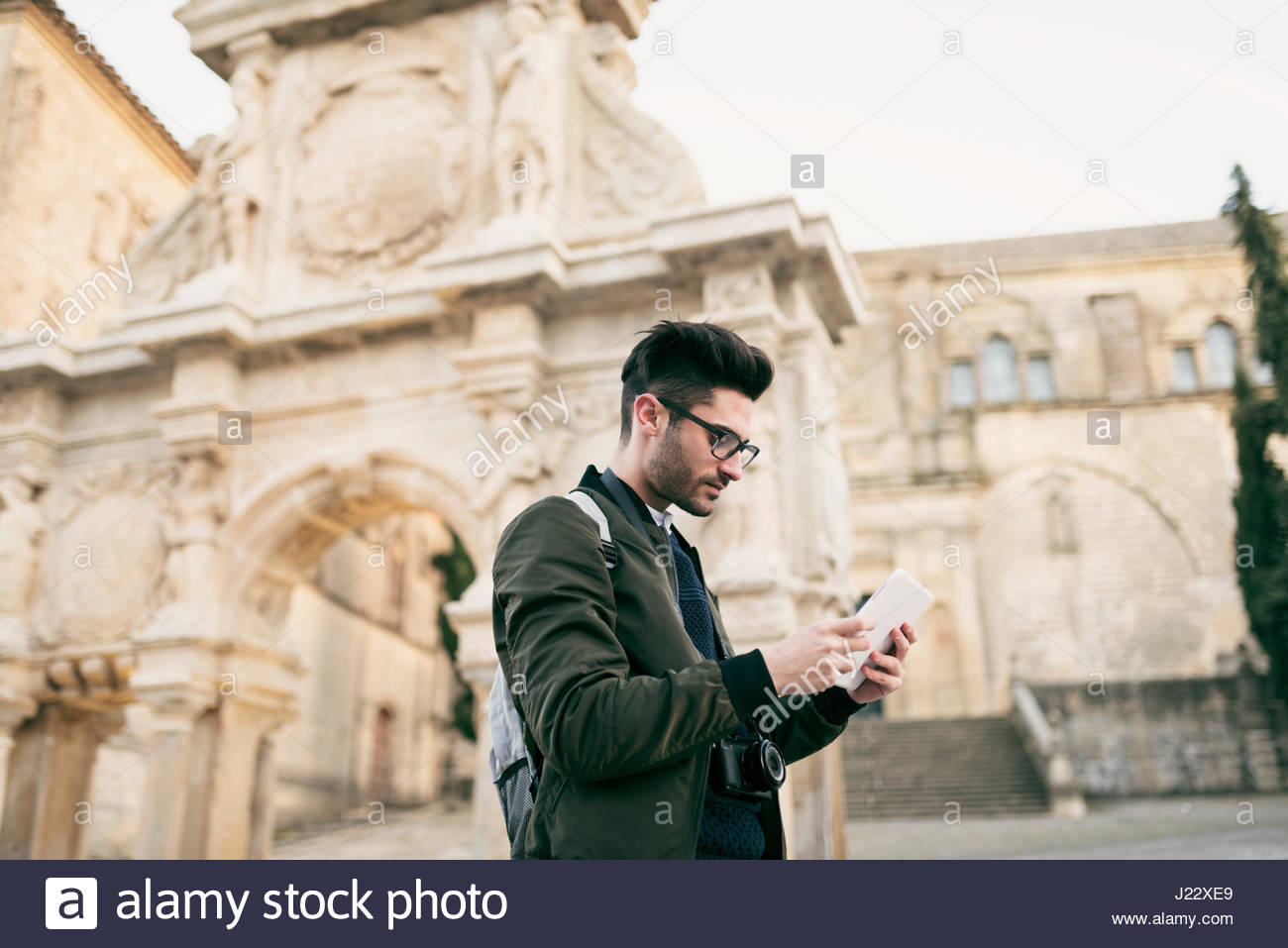 Young mna using tablet on a city break - Stock Image