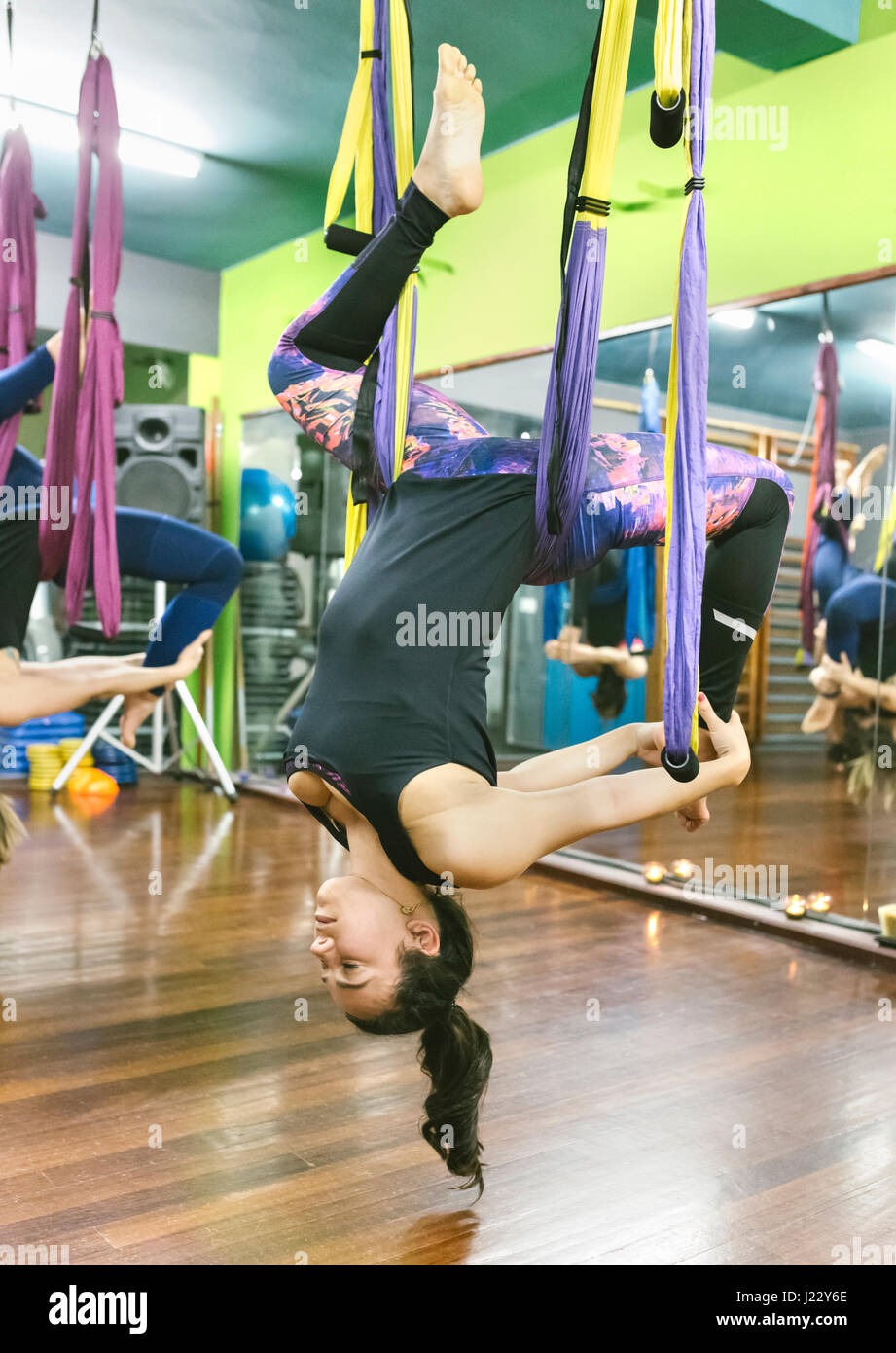 Woman practicing aerial yoga in class - Stock Image