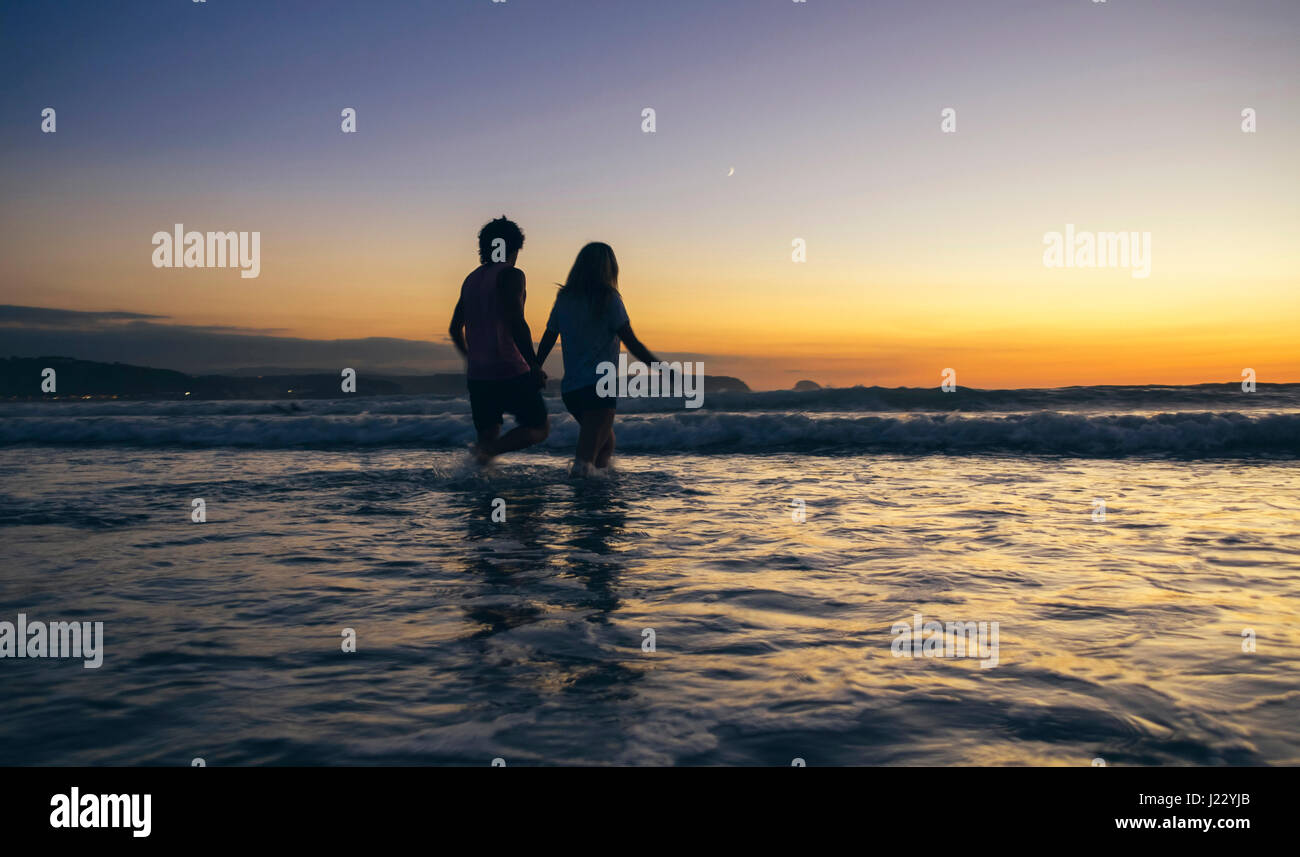 Young couple walking in the sea at dusk - Stock Image