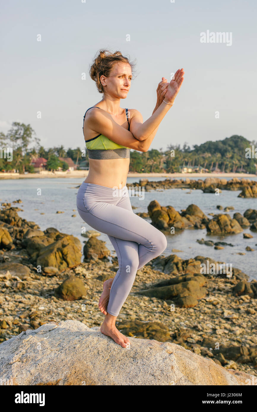 Woman practicing yoga on the beach - Stock Image