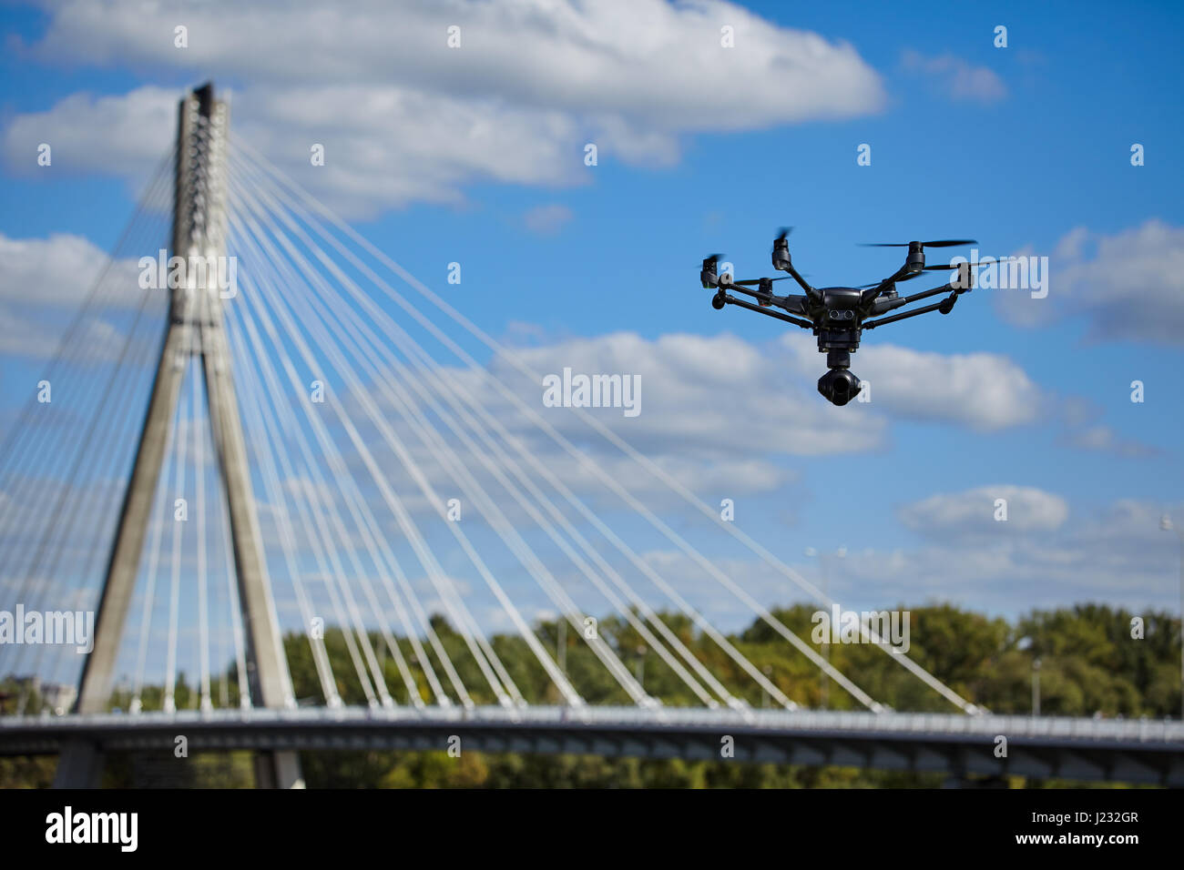 Drone for industrial works flying in sky. - Stock Image