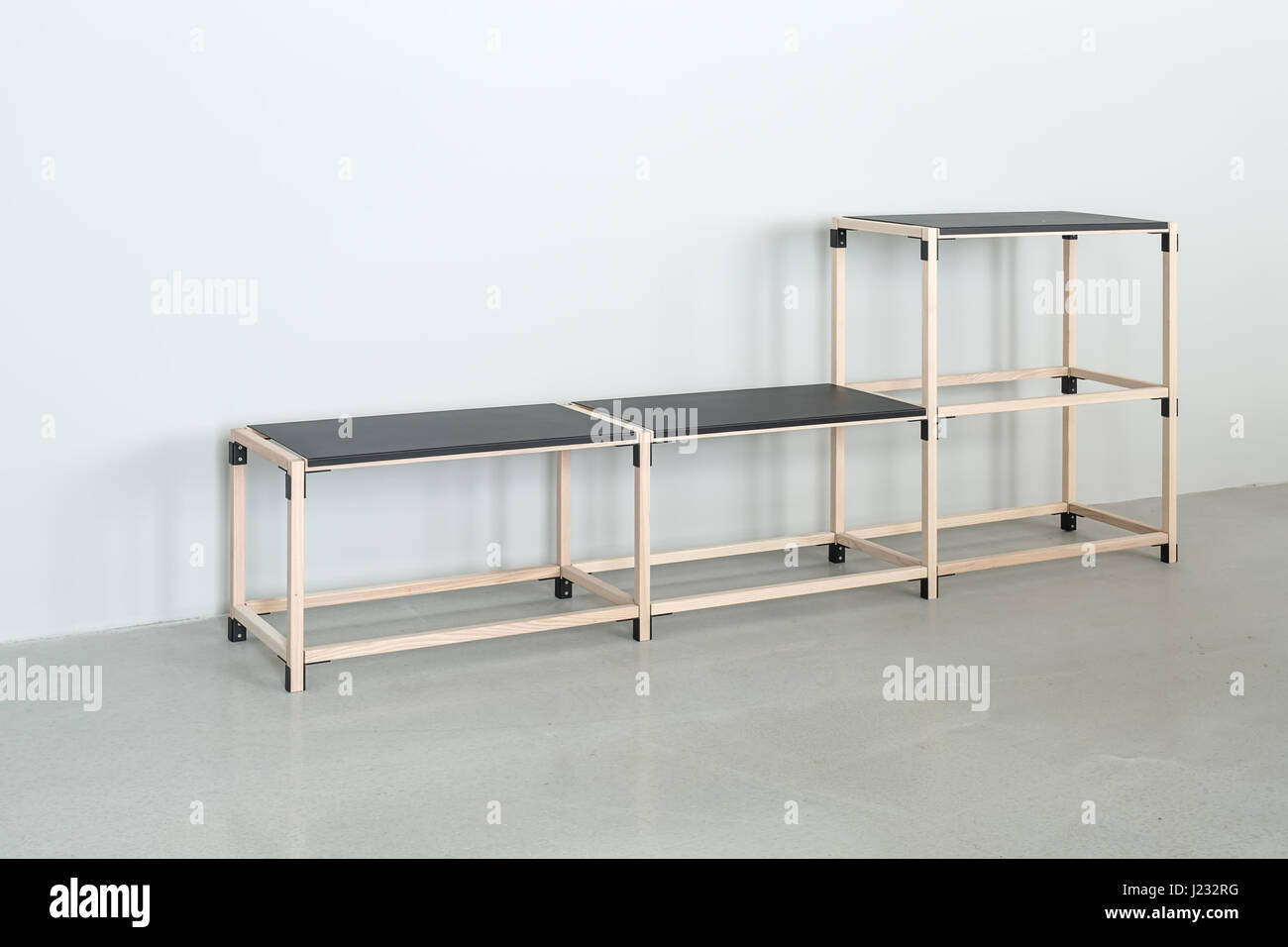Wooden construct with black tabletops - Stock Image