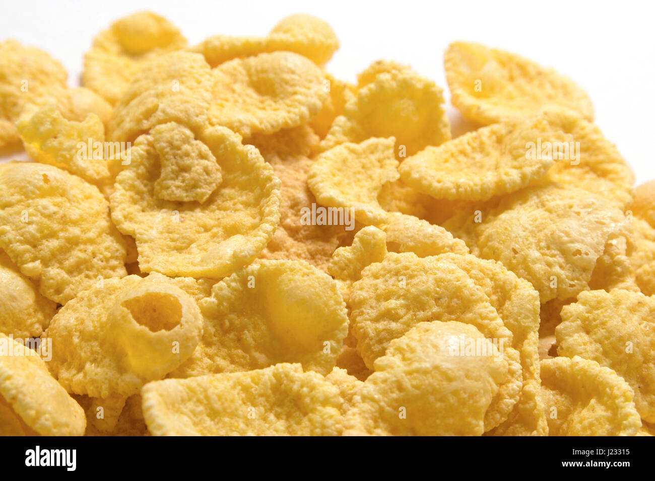 Gold corn flakes heaped on the white table. - Stock Image