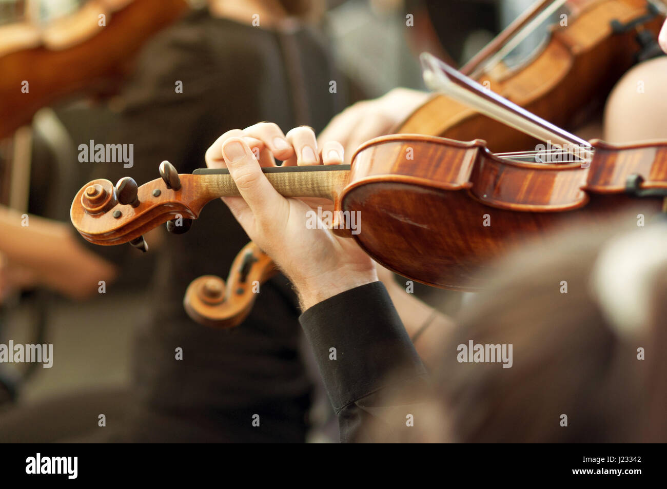 Member of classical music orchestra playing violin on a concert, unrecognizable musician with string instrument, - Stock Image