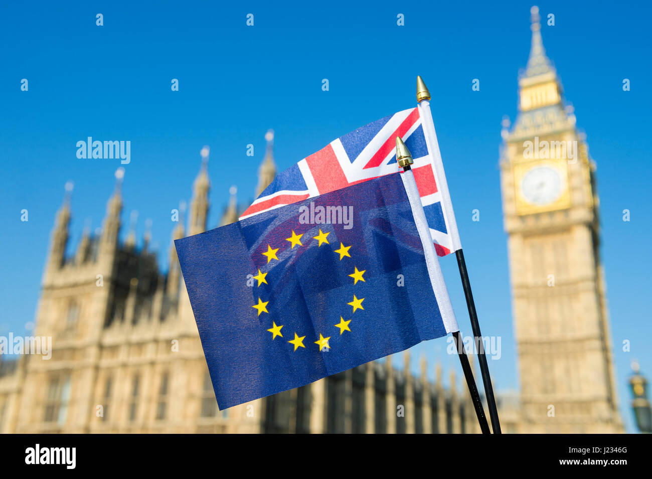 EU European and UK United Kingdom flags fly together in solidarity in bright blue sky in front of the Houses of - Stock Image