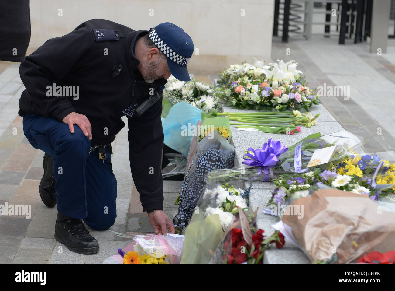 Floral tributes for PC Keith Palmer who was killed on 21st March in a terrorist attack, are placed outside New Scotland - Stock Image