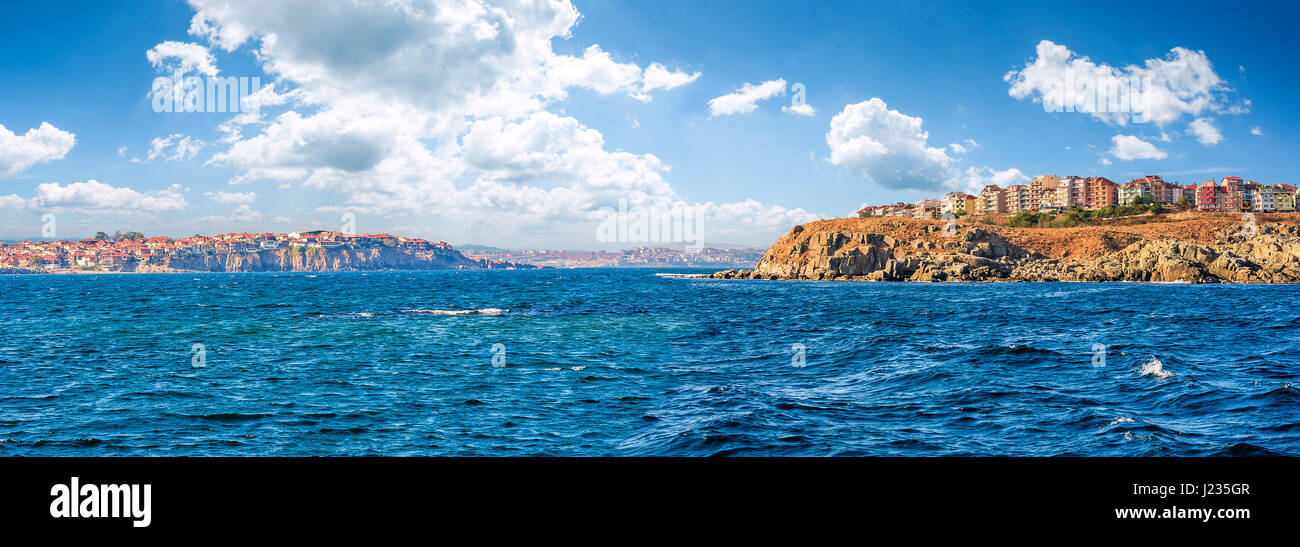 composite summer seascape. panoramic view of old resort town on a rocky cliff above the seashore. blue and calm - Stock Image