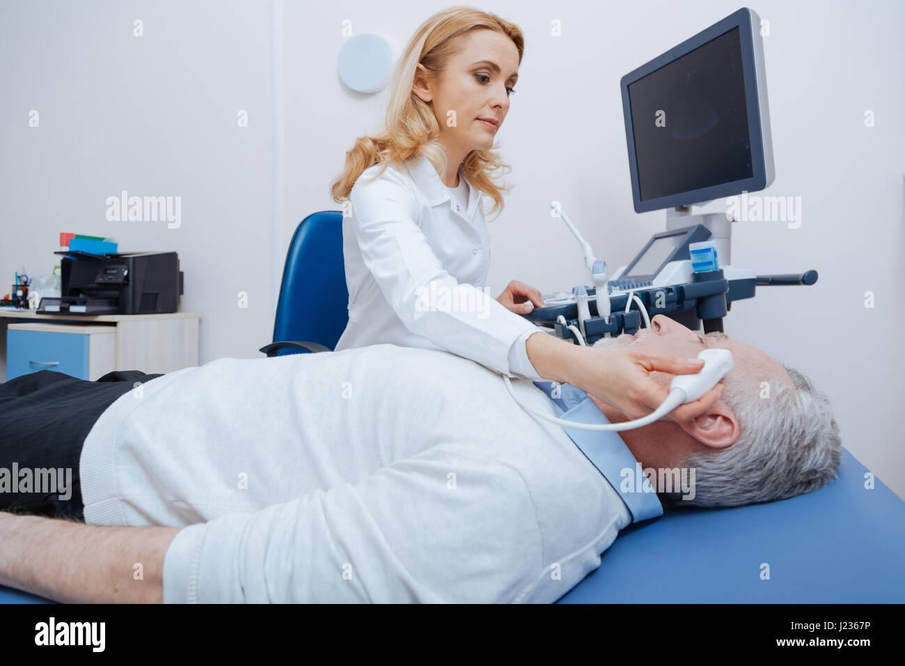 Female sonographer providing brain ultrasound in the hospital - Stock Image