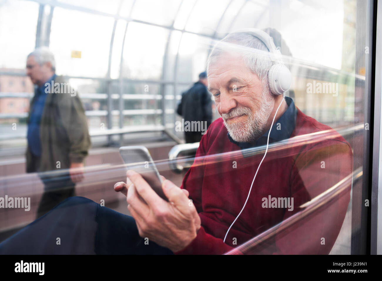 Senior man with smartphone and headphones sitting in passage. - Stock Image