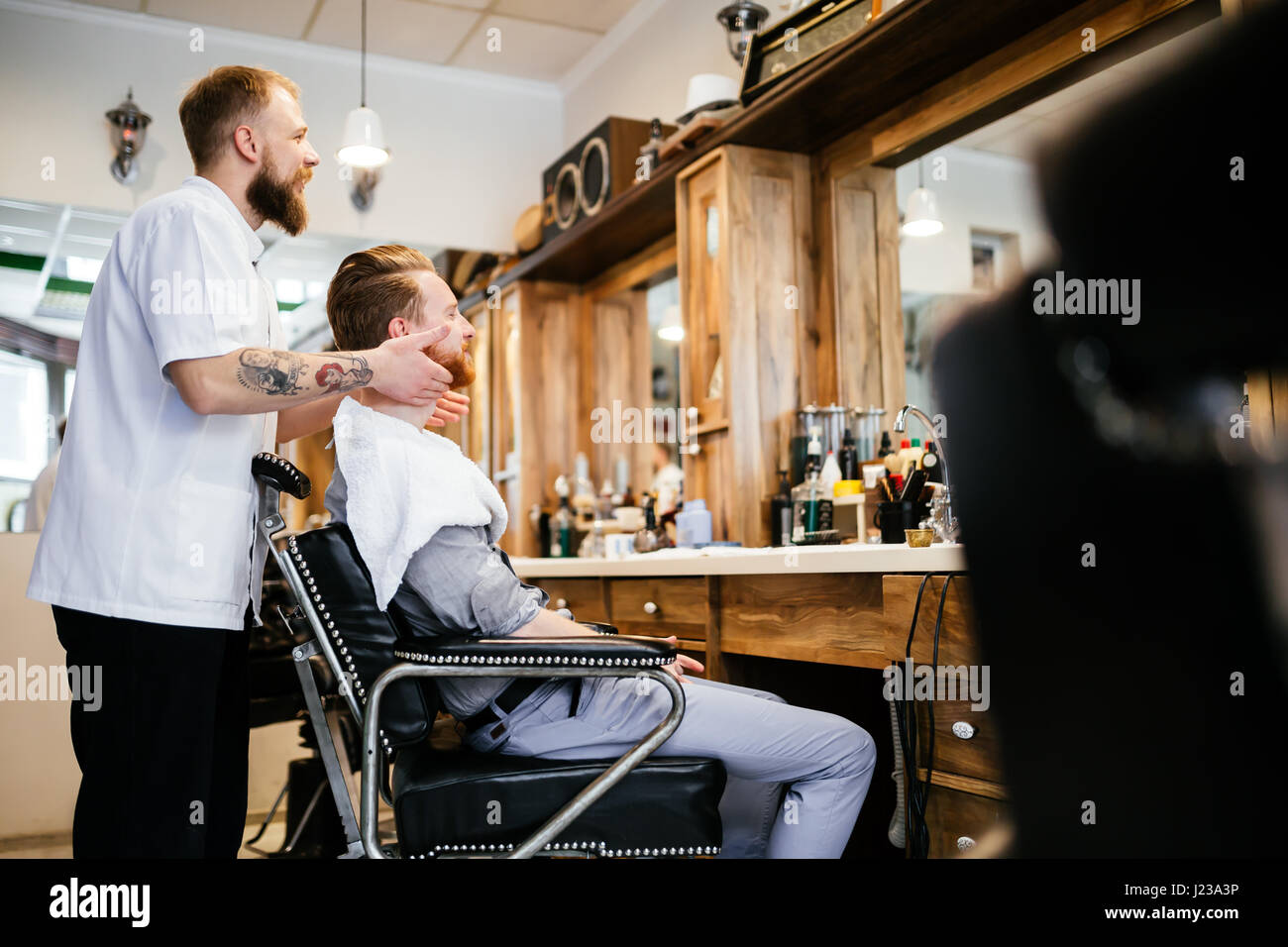 Hair beard and mustache treatment in barber shop - Stock Image