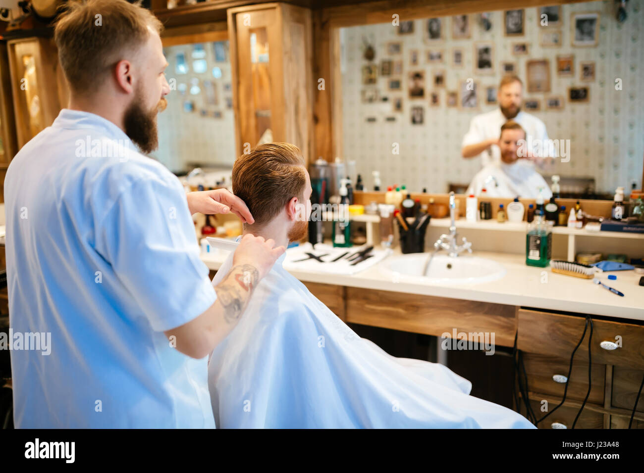Combing of hair and styling in barber shop - Stock Image