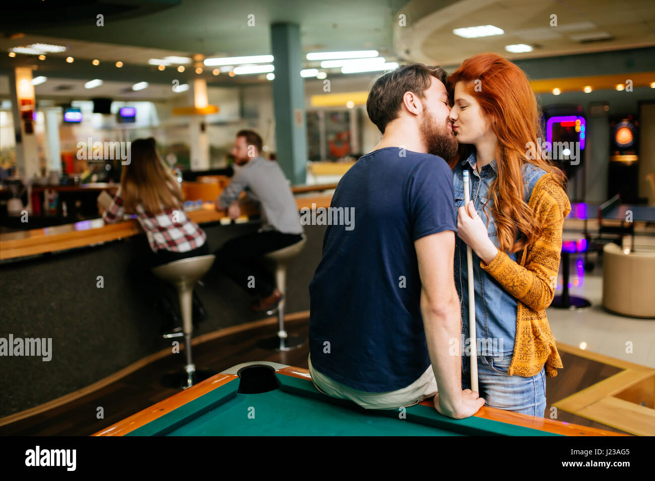 Beautiful couple kissing in billiards bar on their date - Stock Image