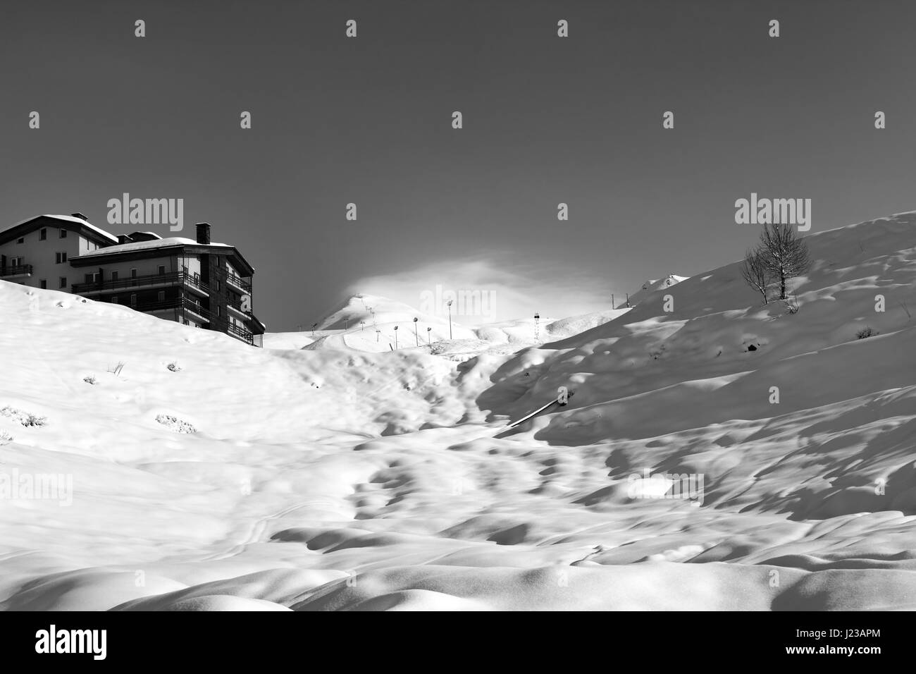 Black and white view on off-piste slope and hotel in winter mountains. Caucasus Mountains, Georgia, region Gudauri. - Stock Image