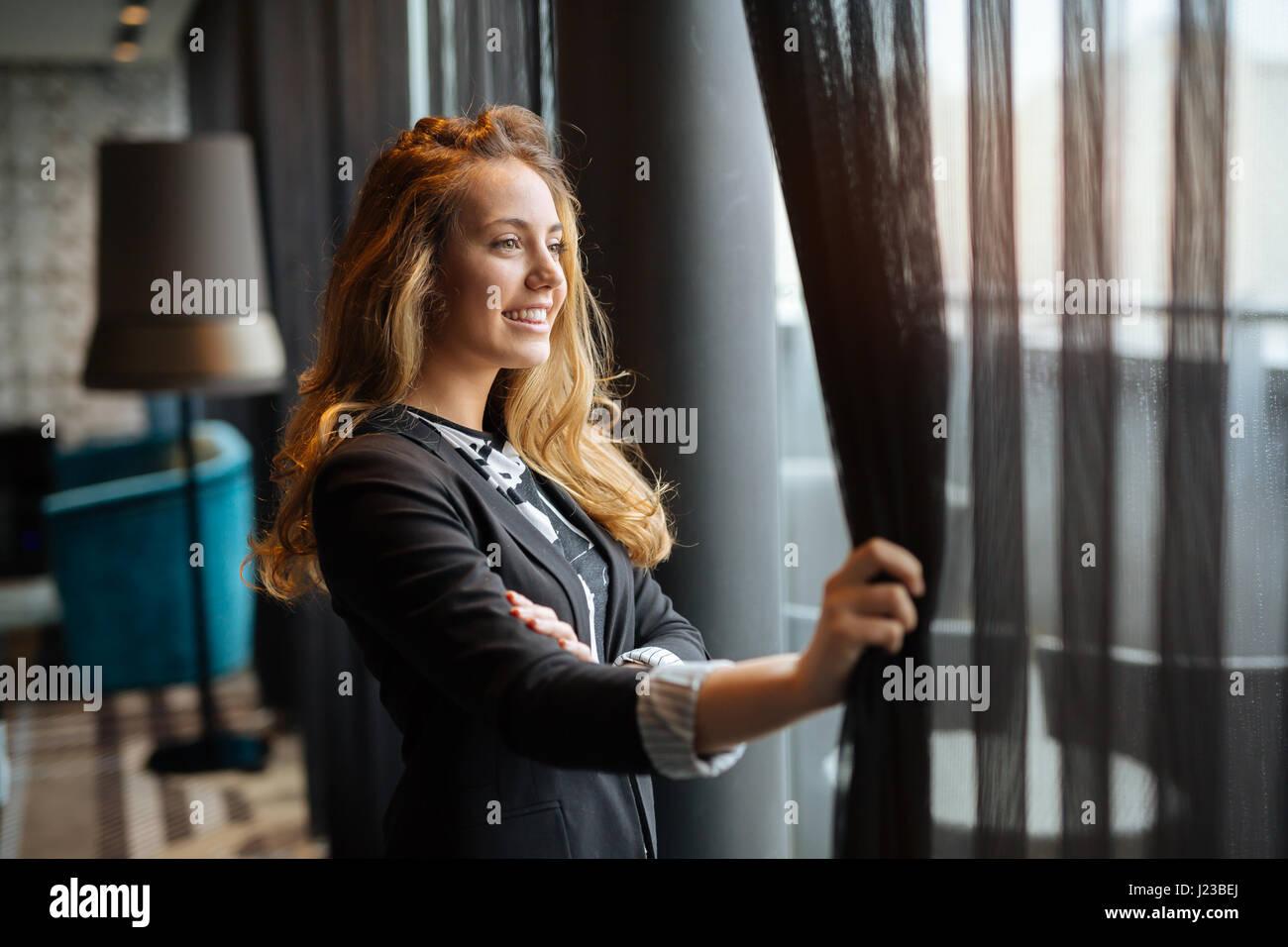 Glamorous happy  woman  staring through window - Stock Image