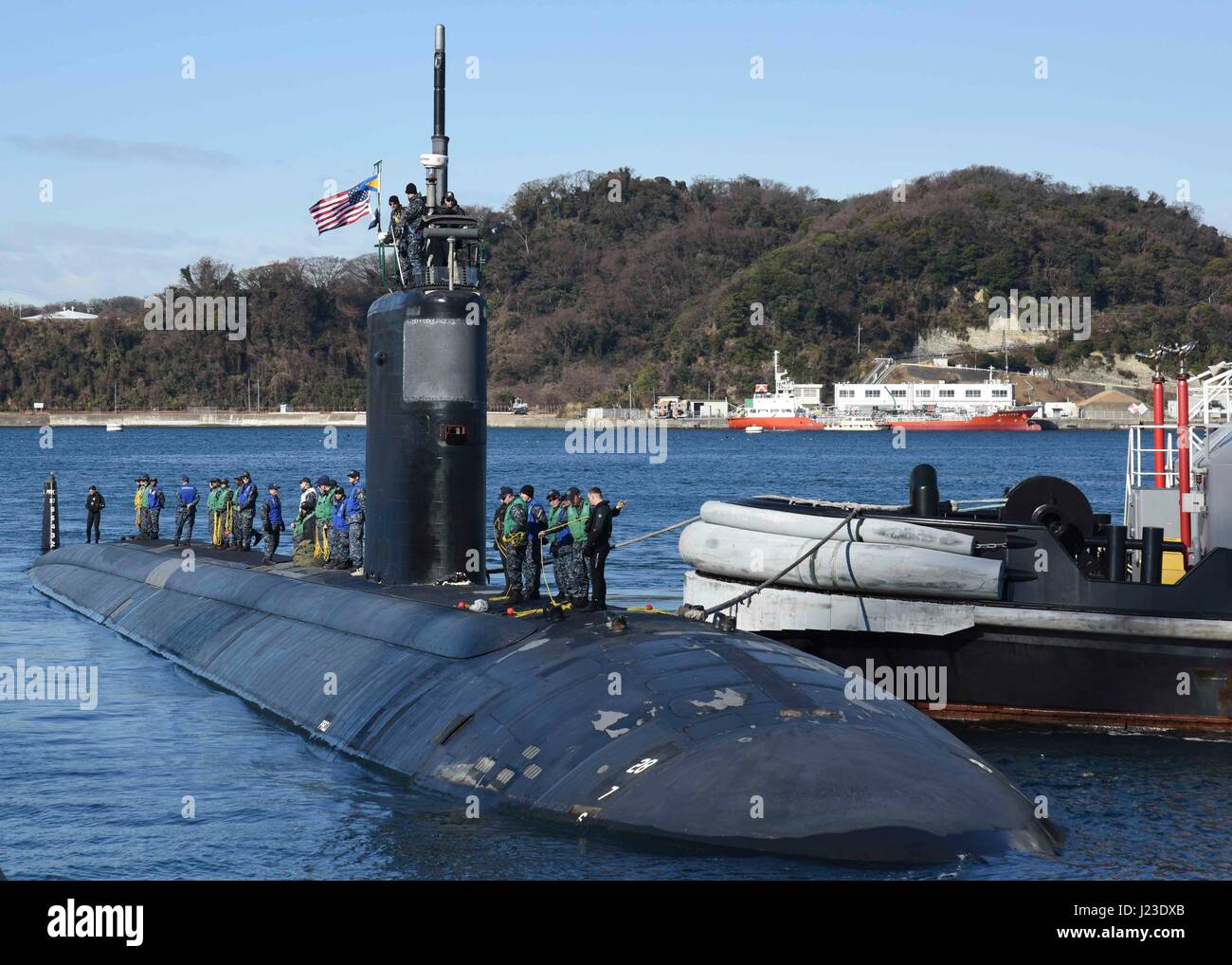 U.S. sailors stand on the surface of the USN Los Angeles-class attack submarine USS Topeka as it moors at Fleet - Stock Image