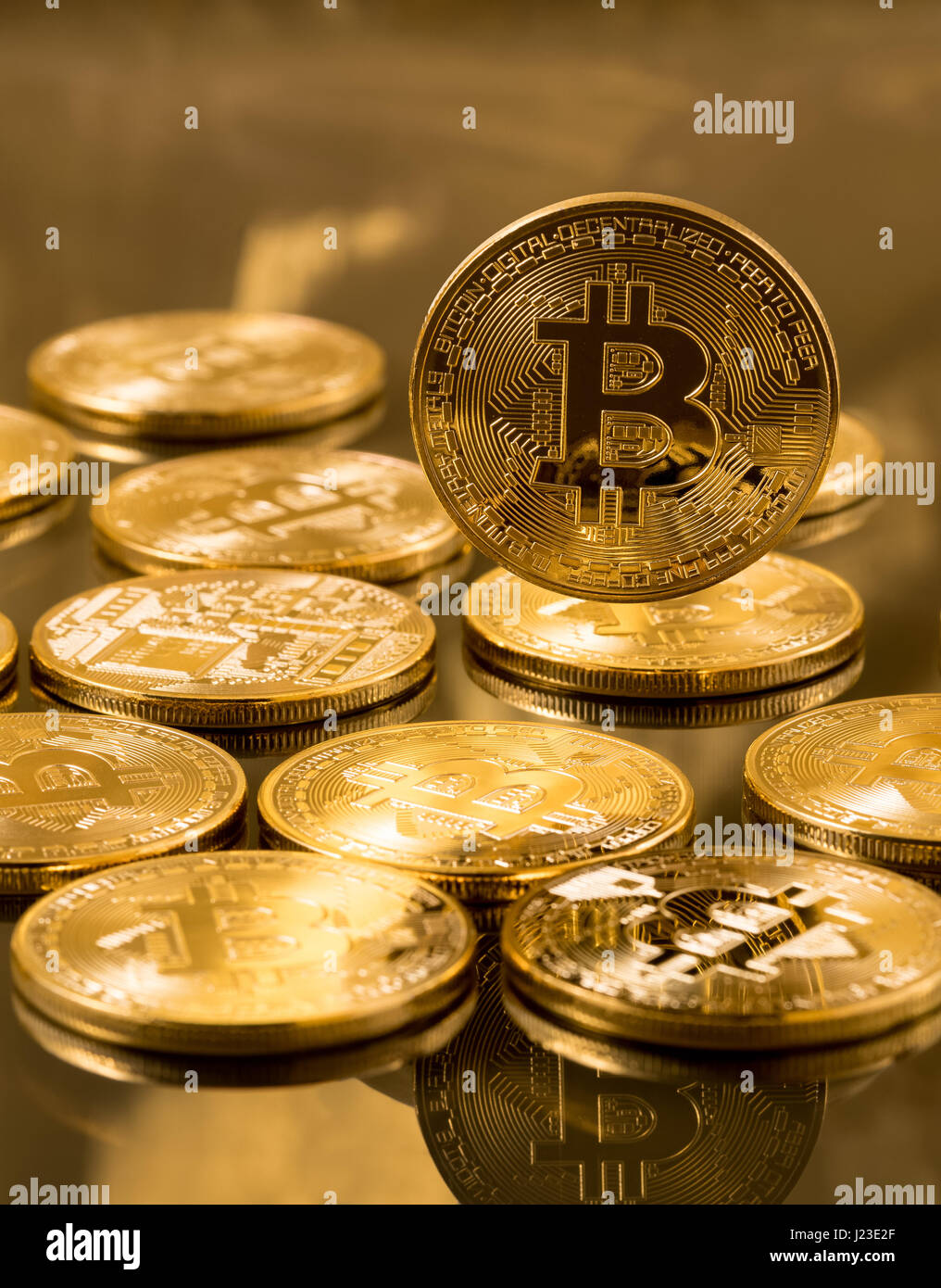Stack of bitcoins on gold background - blockchain and cyber currency concept - Stock Image