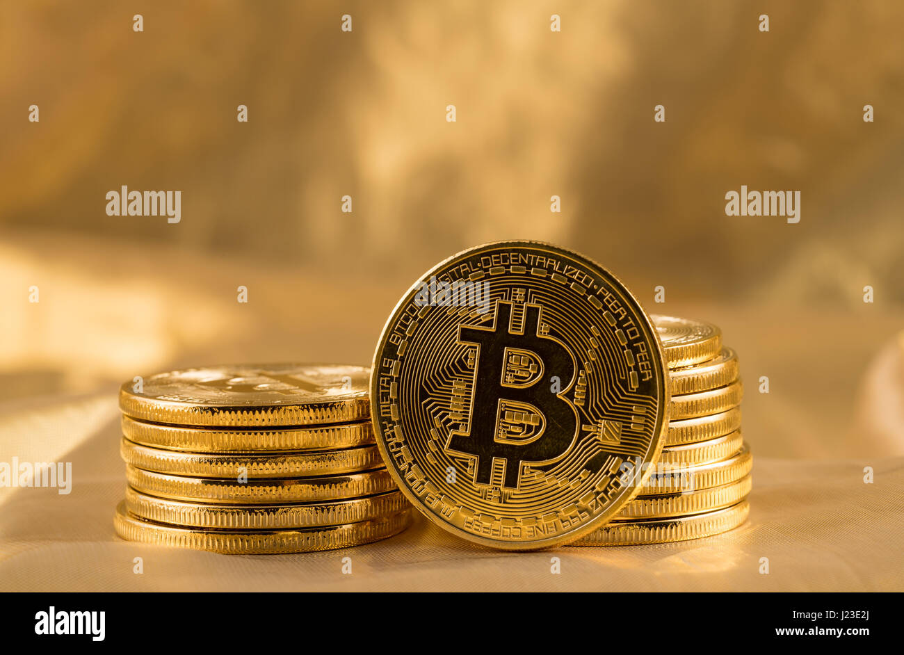 Stack of bit coins or bitcoin on gold background to illustrate blockchain and cyber currency - Stock Image