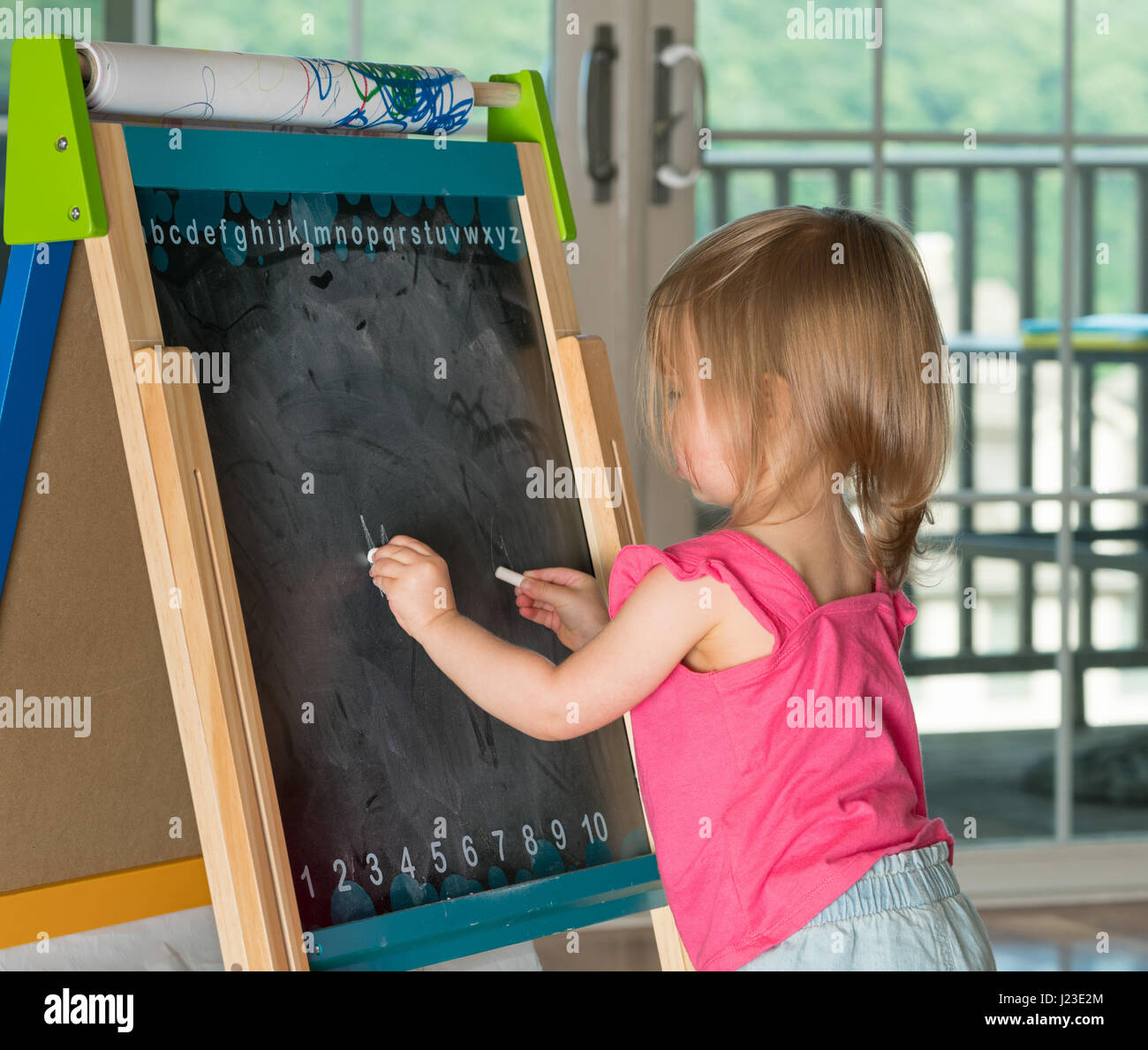 Young child learning to write and writing with chalk on a blackboard - Stock Image