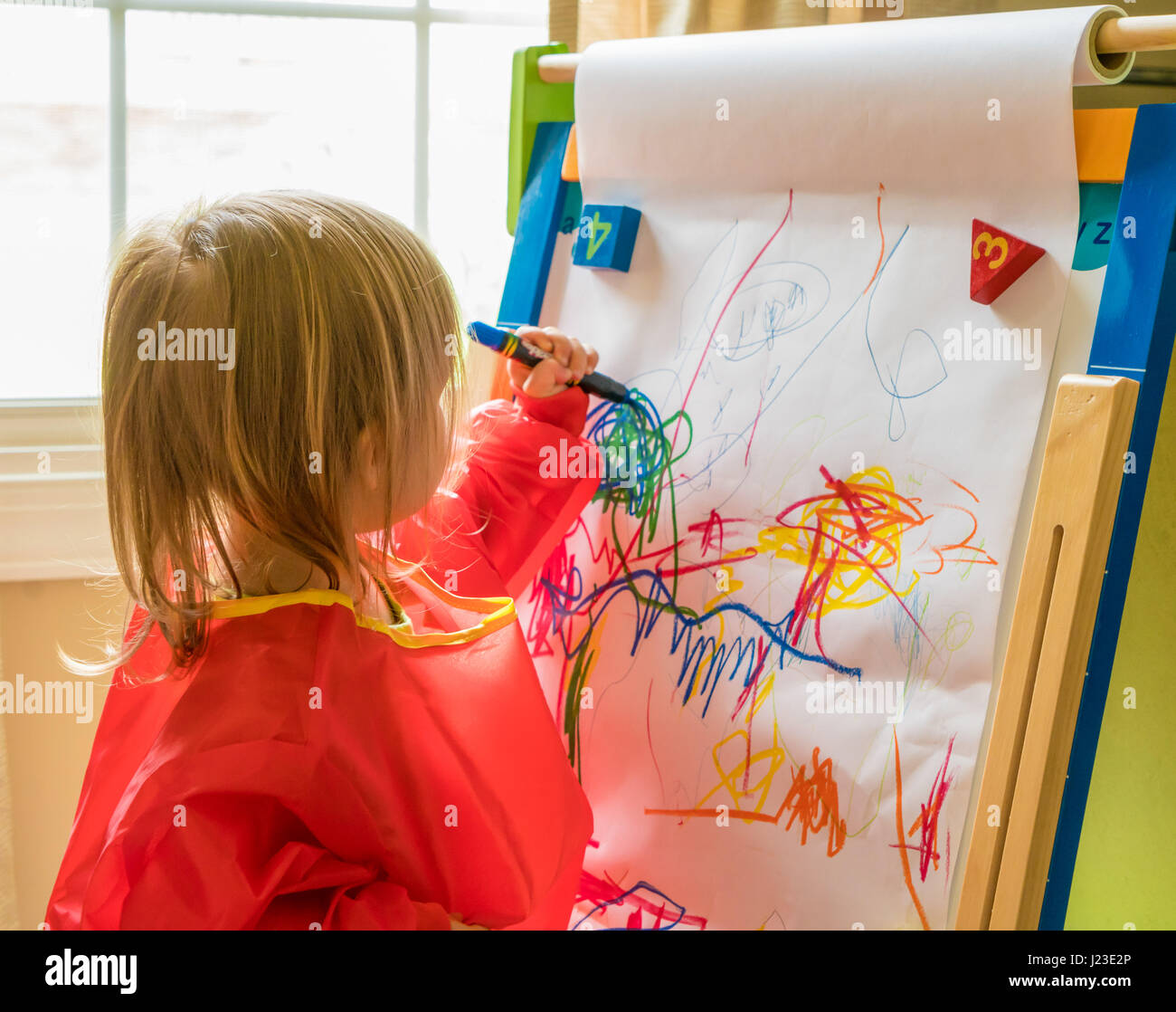 Young child drawing with crayon left handed on an easel during nursery playtime - Stock Image