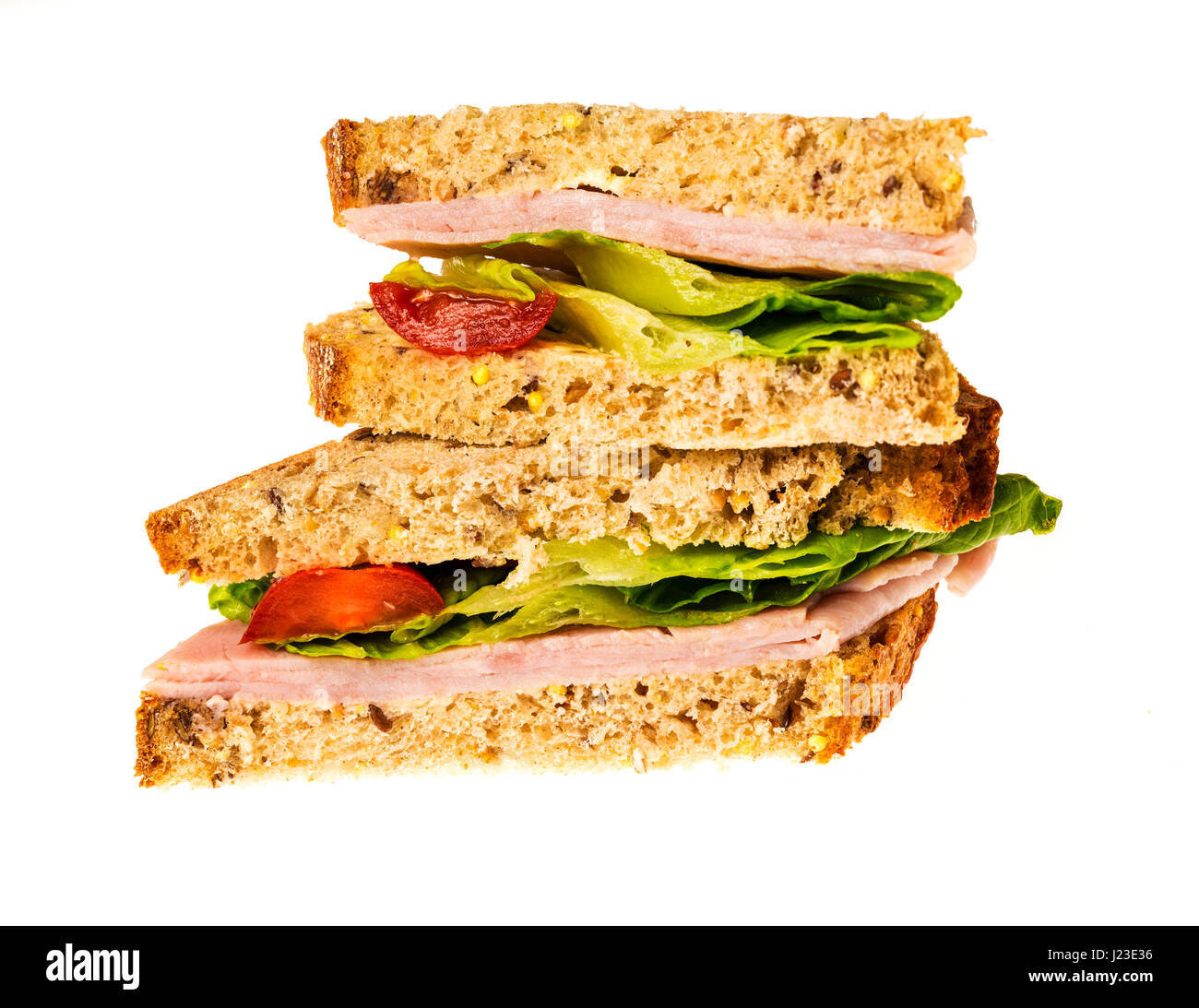 Home made ham, lettuce and tomato sandwich on brown bread - Stock Image
