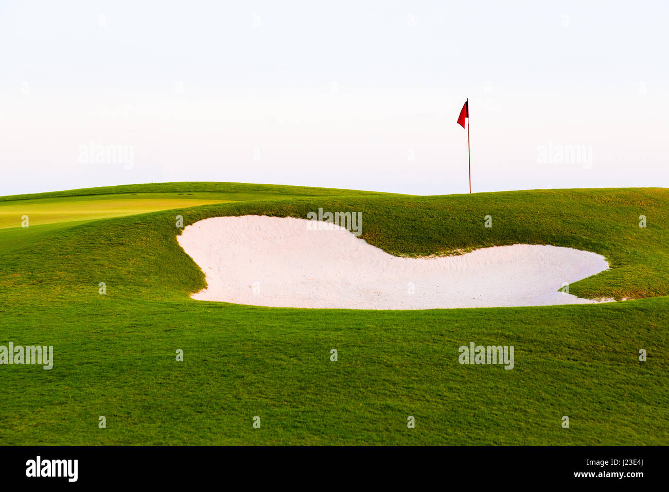 Red flag of golf hole above sand trap or golf course bunker - Stock Image