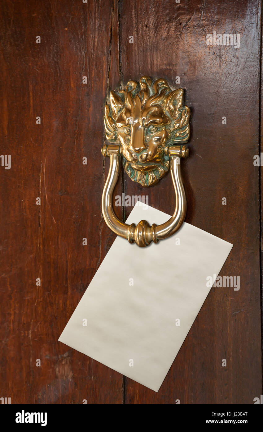 Blank Envelope with space for text placed under a brass lion head door knocker on old oak door - Stock Image