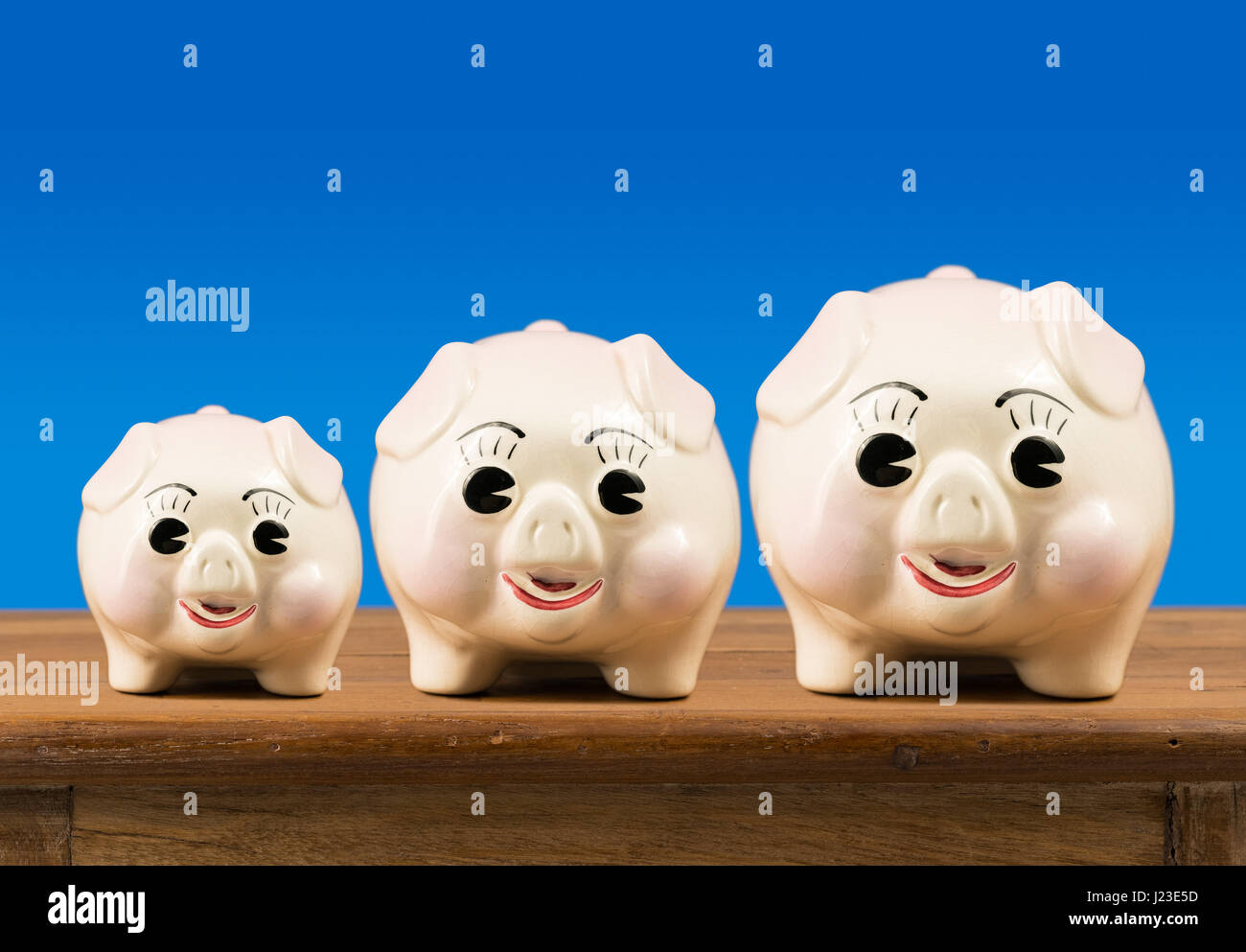 Three piggy banks growing in size in a row - Stock Image