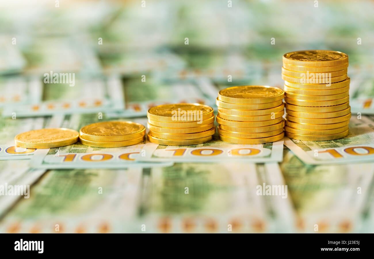 Stack of American gold eagle gold bullion coins pile rising growth on new design of US currency hundred dollar bills - Stock Image