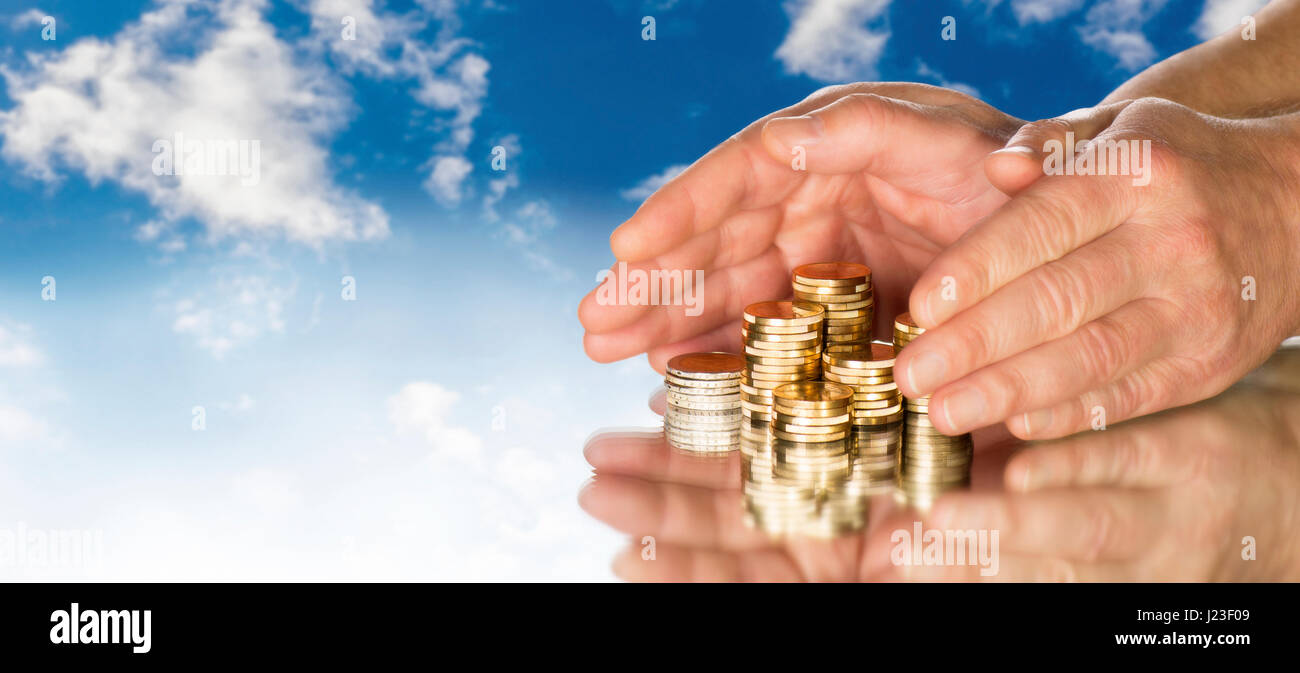 Hands include several stacks of coins in front of blue sky. - Stock Image
