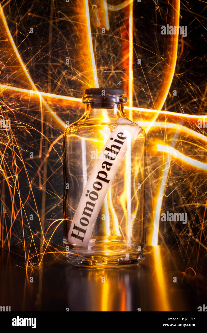 Glass with the word homeopathy and stray sparks - Stock Image