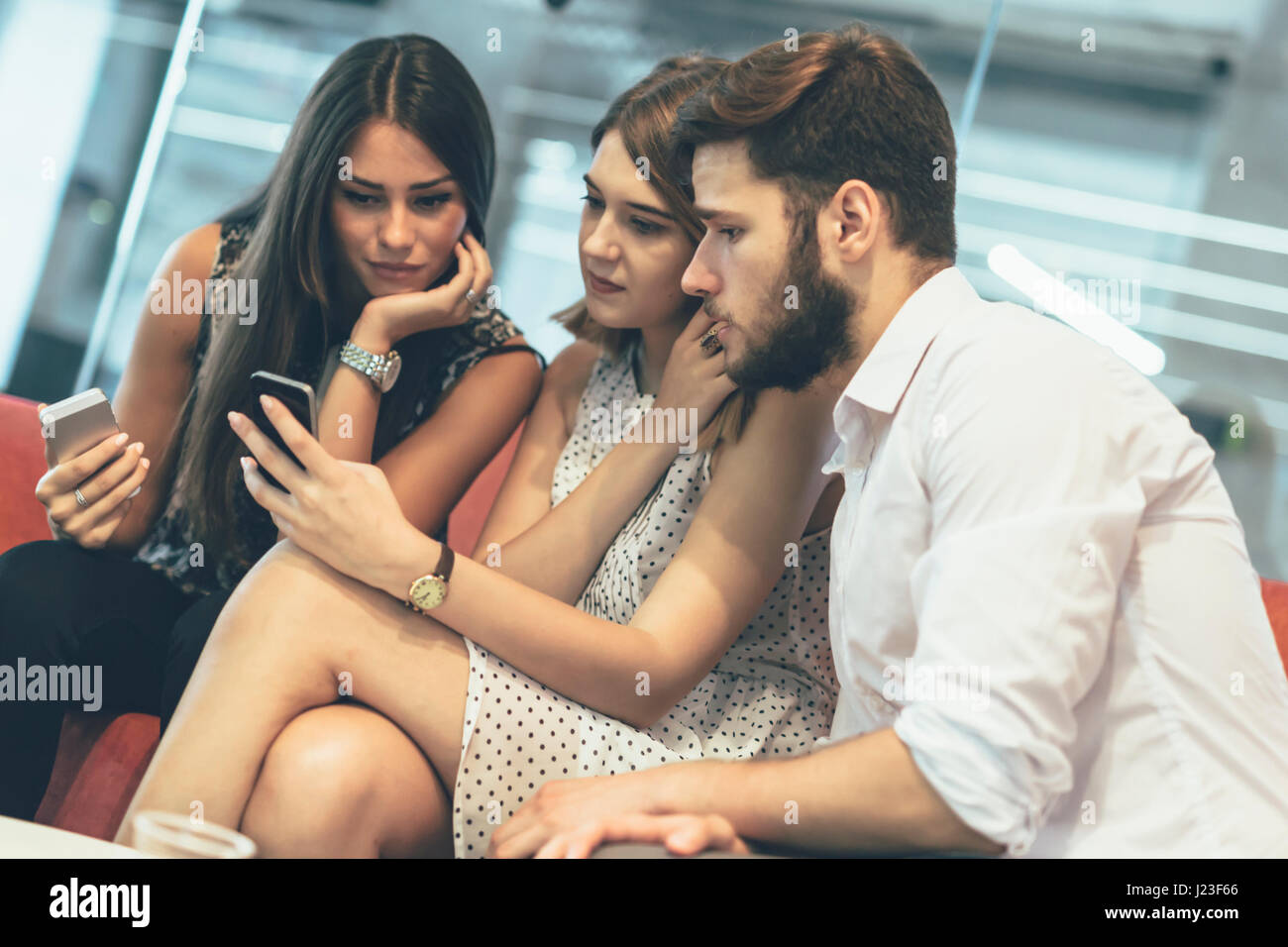 Young people using their cell phones and staying always connected - Stock Image